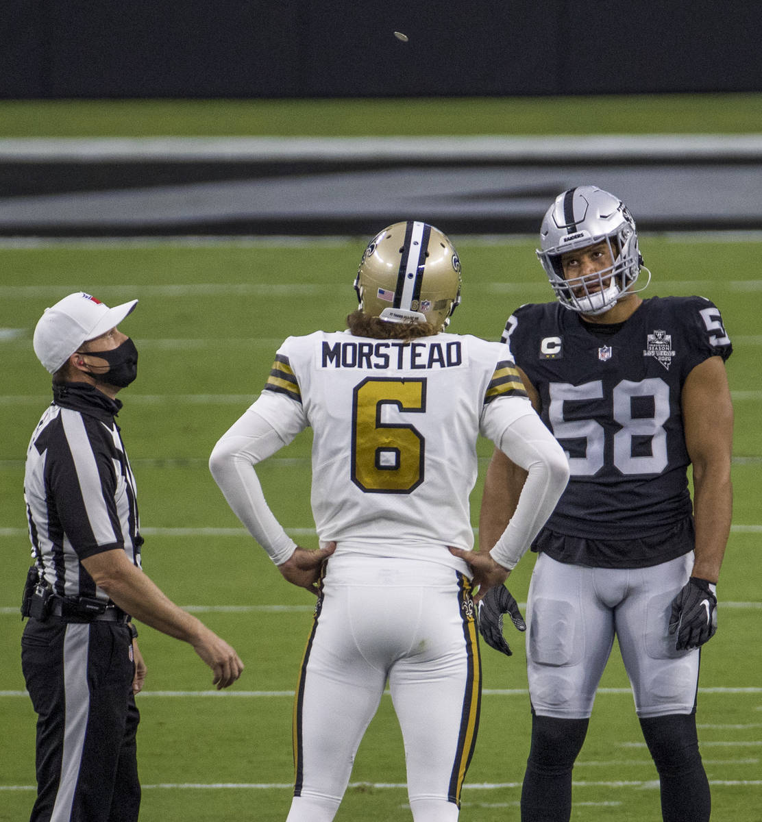 Las Vegas Raiders linebacker Kyle Wilber (58, right) looks up to the coin toss with New Orleans ...