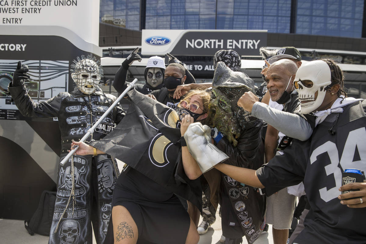 New Orleans Saints fan Amy Laughlin is surrounded by Las Vegas Raiders characters as they gathe ...