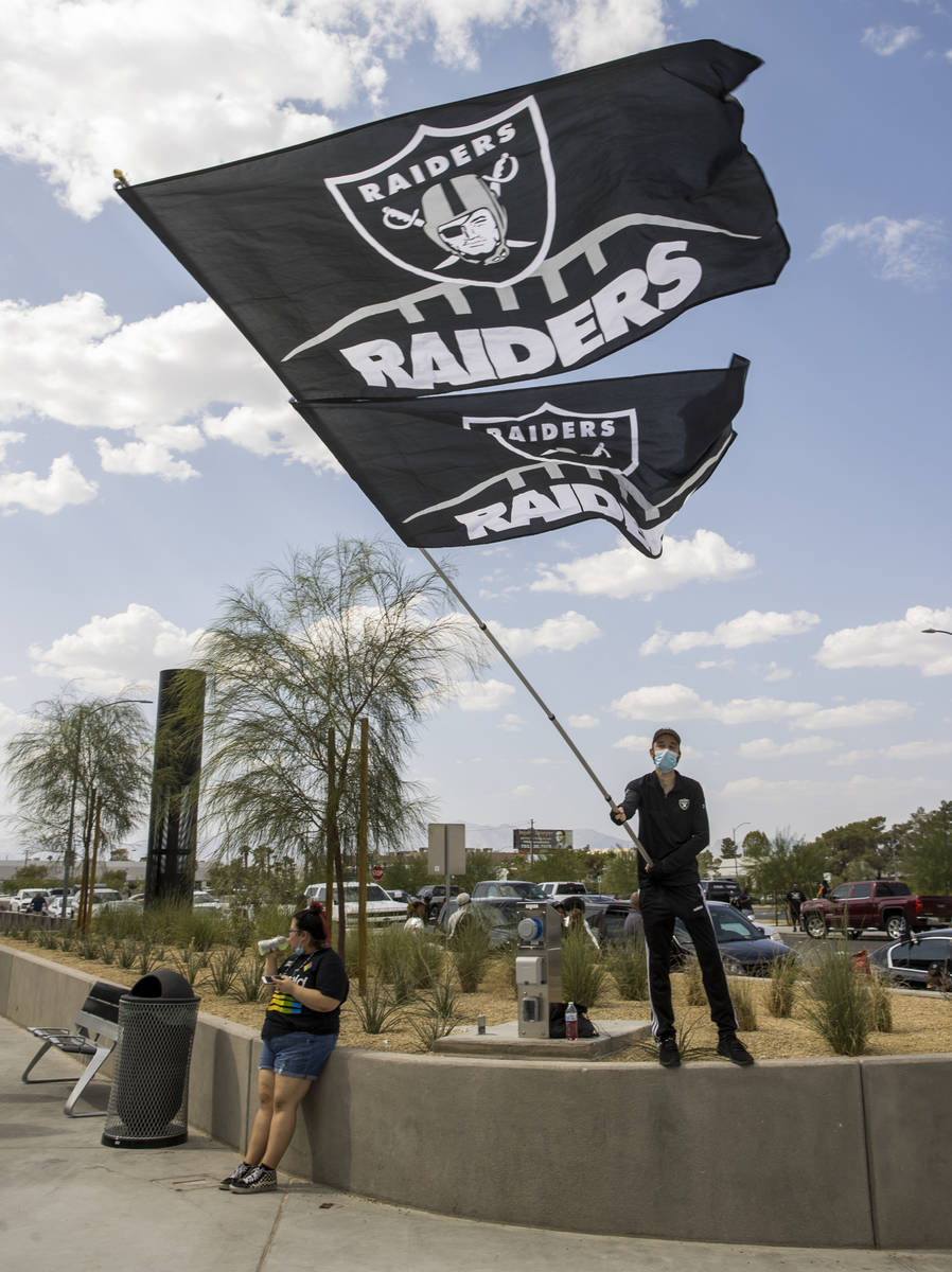 Las Vegas Raiders fan Matt Helfst waves giant flags as he and others gather outside several hou ...