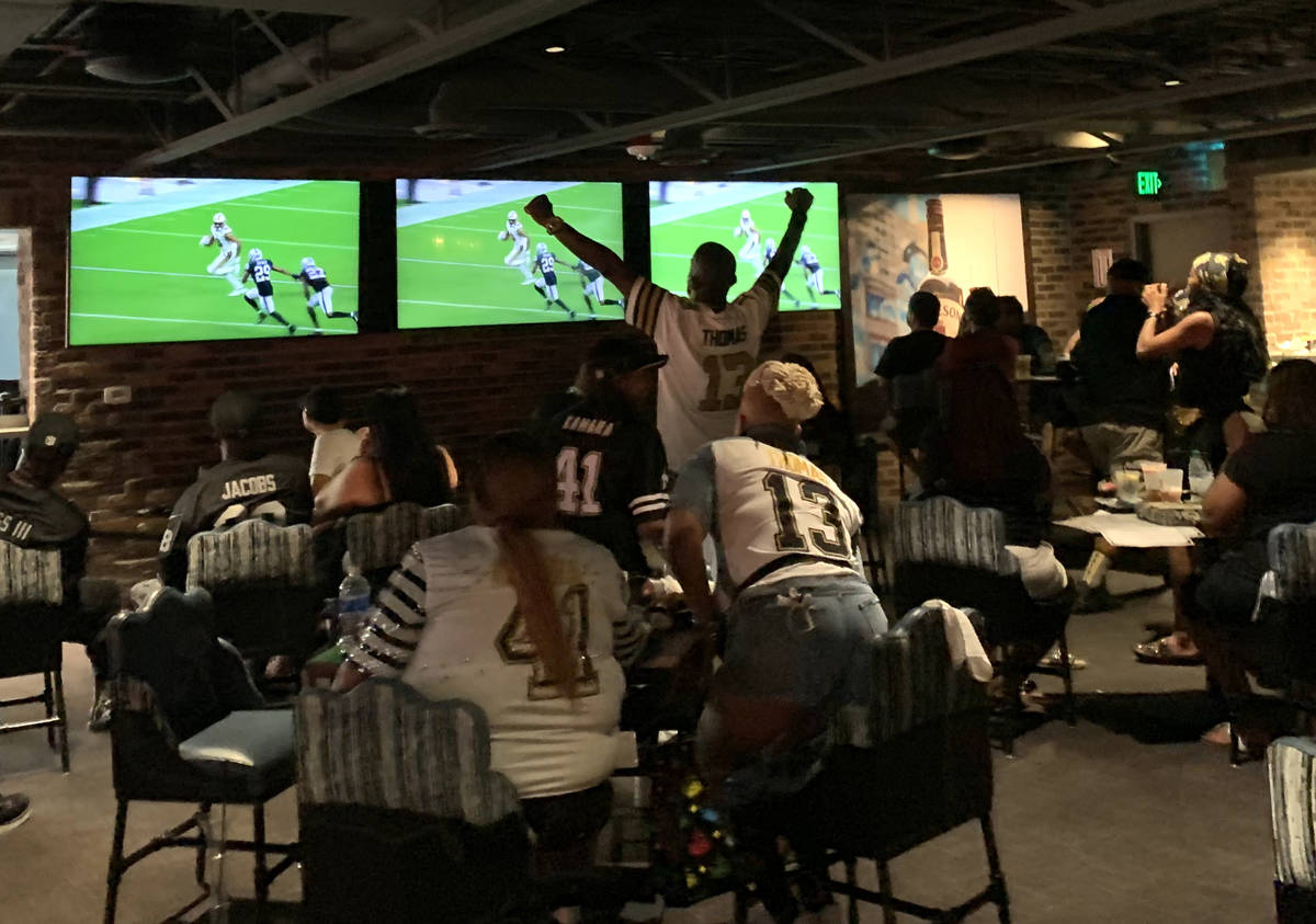 Saints fans applaud during a game at Whiskey Licker Up at Binion's on the Fremont Street Experi ...