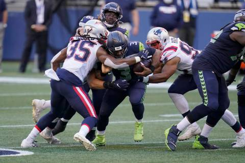 Seattle Seahawks quarterback Russell Wilson is tackled by New England Patriots safety Kyle Dugg ...