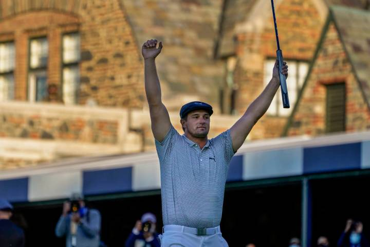 Bryson DeChambeau, of the United States, reacts after sinking a putt for par on the 18th hole t ...