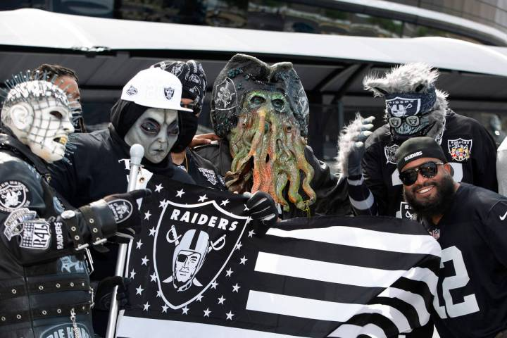 Patrick Beckett of New Jersey poses for a photo with Raiders fans in costumes as fans congregat ...