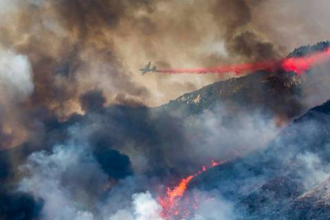 An air tanker drops retardant at a wildfire burns at a hillside in Yucaipa, Calif., Saturday, S ...