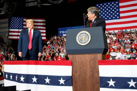 President Donald Trump listens Fox News' Sean Hannity speak. (AP Photo/Carolyn Kaster)