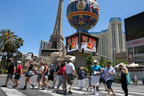 Tourists cross Las Vegas Boulevard near Paris hotel-casino on Friday, July 3, 2020, in Las Vega ...