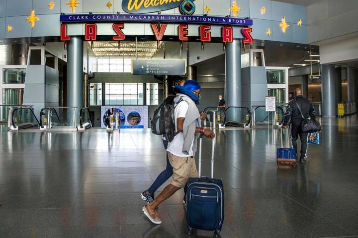 Passengers make their way through Terminal 1 as COVID-19 safety precautions continue at McCarra ...
