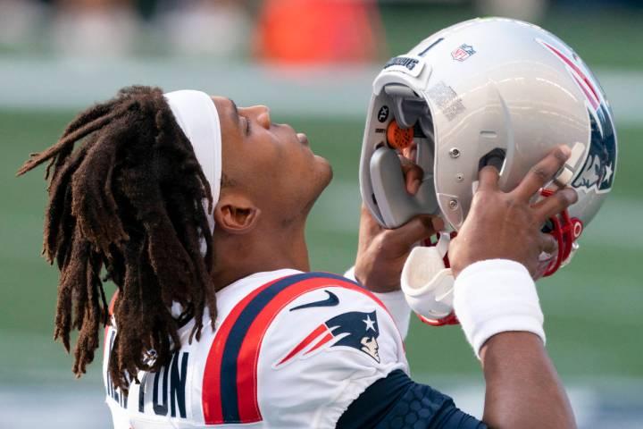 New England Patriots quarterback Cam Newton puts on his helmet before an NFL football game agai ...