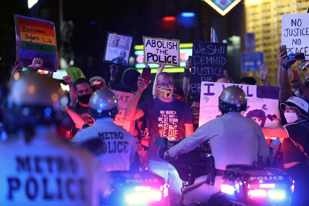 Attorney Jonathan MacArthur holds up his cellphone while facing police in downtown Las Vegas on ...