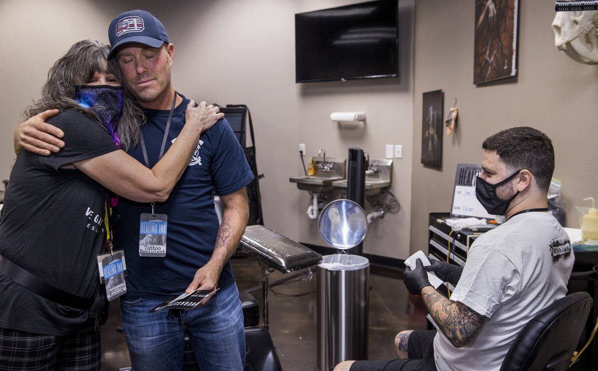 Terri Keener with the Vegas Strong Resiliency Center, left, hugs Dean McAuley with tattoo artis ...