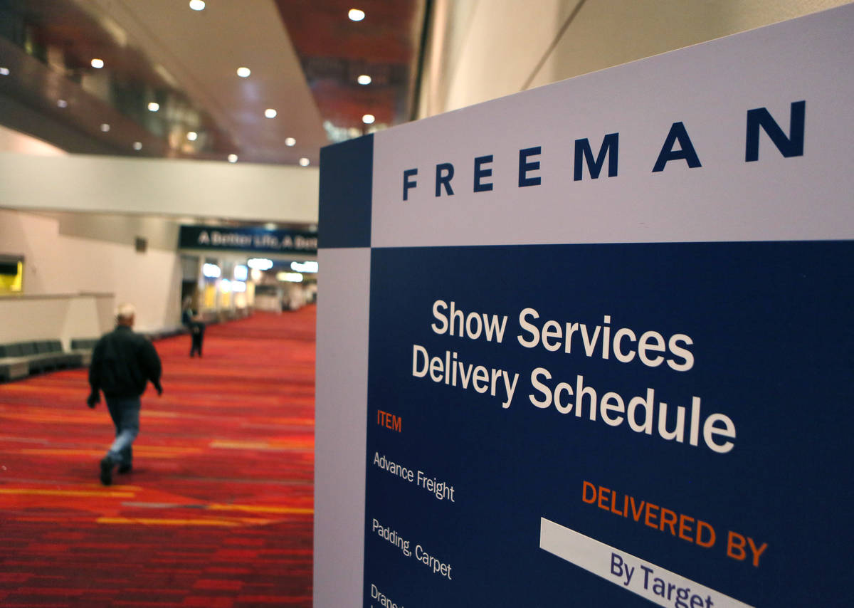 A man walks by a Freeman delievery schedule sign during preparations for the Consumer Electroni ...