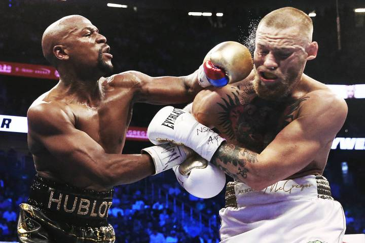 Floyd Mayweather, left, lands a left hook on the jaw of Conor McGregor on Saturday, Aug 26, 201 ...
