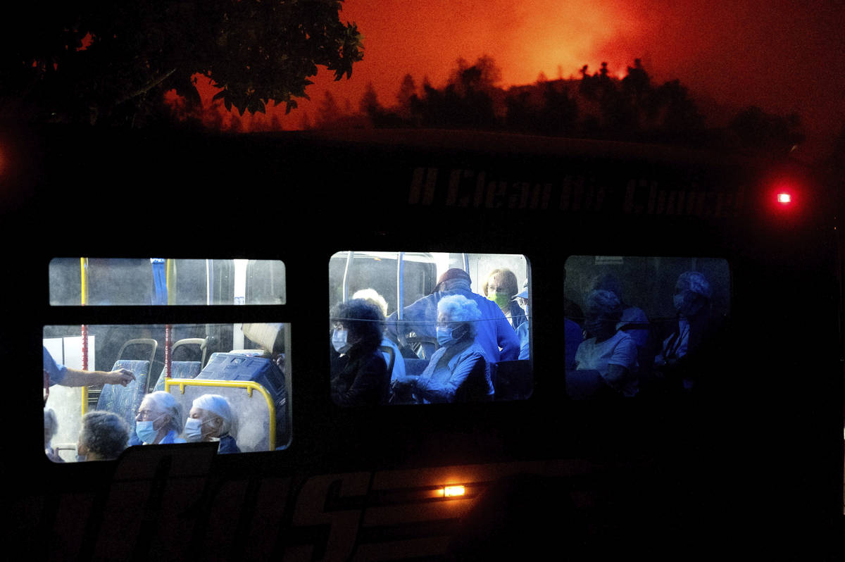 Residents of the Oakmont Gardens senior home evacuate on a bus as the Shady Fire approaches in ...