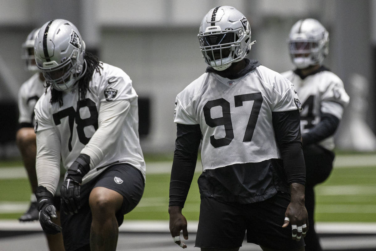 Raiders defensive tackle Maliek Collins (97) stretches during an NFL football training camp pra ...