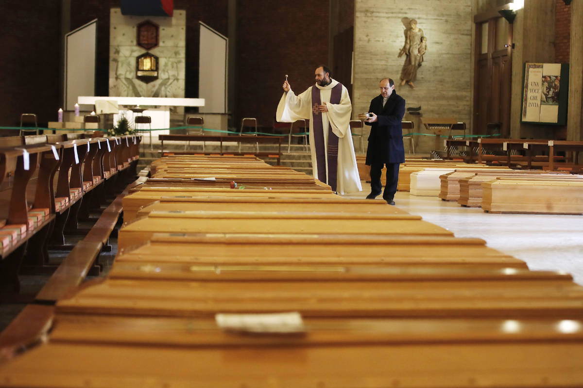 In this March 28, 2020, file photo, Don Marcello Crotti, left, blesses the coffins with Don Mar ...
