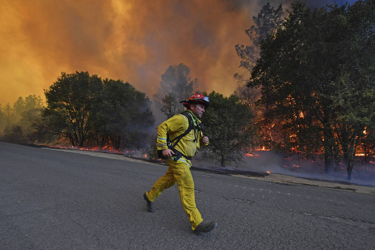 A firefighter runs to his firetruck while protecting a home along Crystal Springs Road while ba ...
