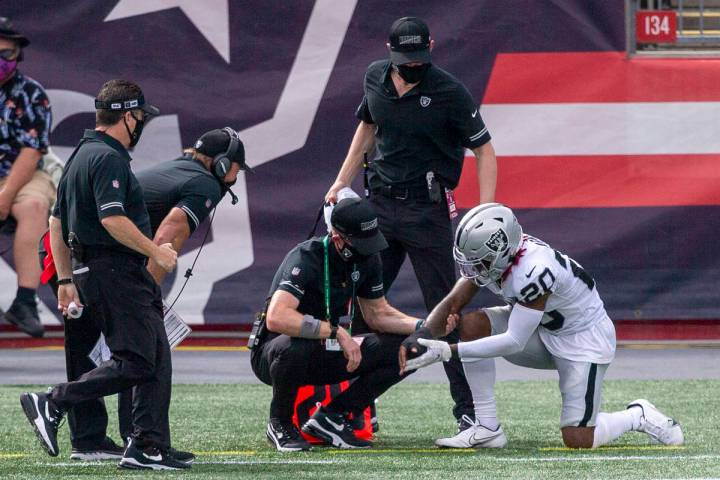 Las Vegas Raiders cornerback Damon Arnette (20) has his right wrist looked at by trainers and h ...