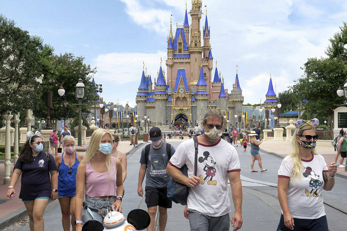 Guests wear masks as required to attend the official reopening day of the Magic Kingdom at Walt ...
