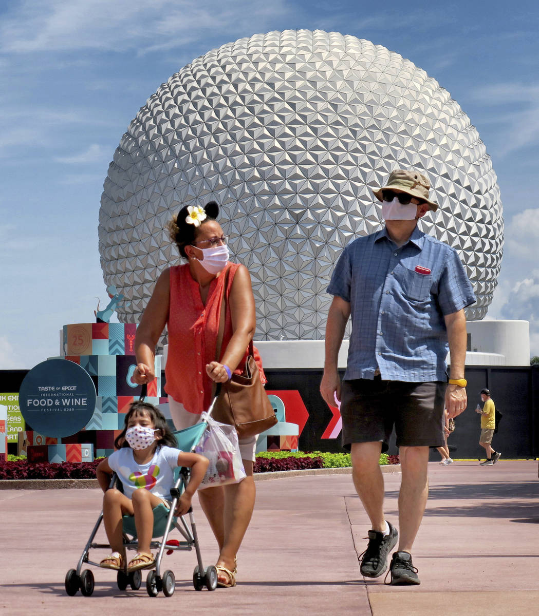 Guests arrive to attend the official re-opening day of Epcot at Walt Disney World in Lake Buena ...
