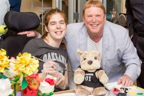 Las Vegas Raiders owner Mark Davis is shown with Opportunity Village client Sarah Brown during ...