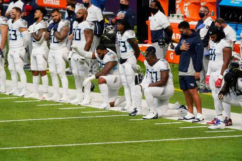 Members of the Tennessee Titans take part in the national anthem before an NFL football game ag ...