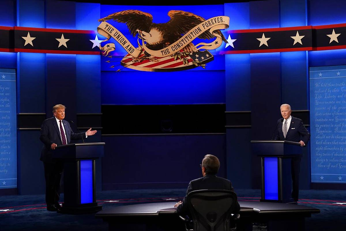 Moderator Chris Wallace of Fox News listens as President Donald Trump and Democratic candidate ...