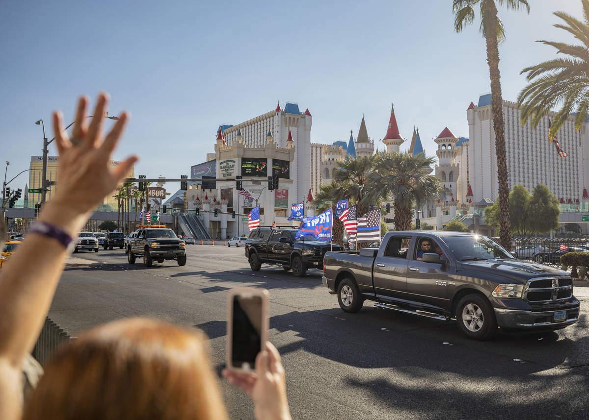 Individuals cheer as a caravan of Trump supporters ride down the Las Vegas Strip, on Wednesday, ...
