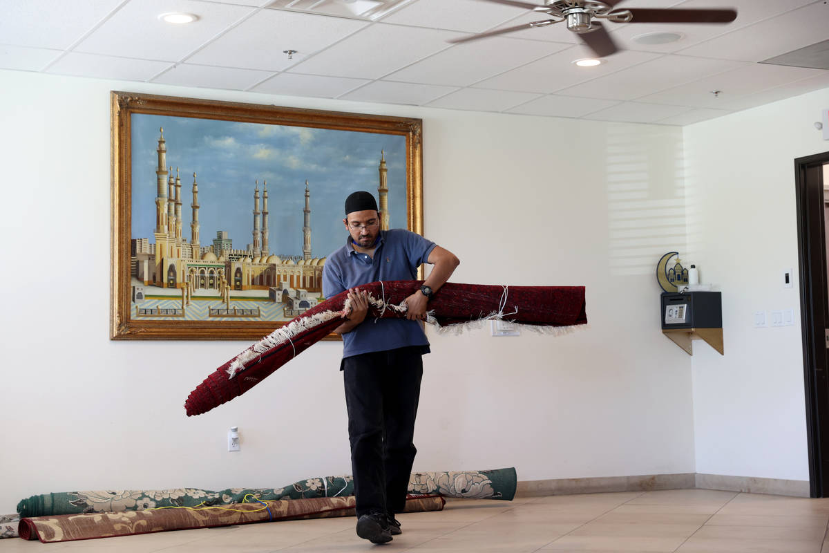 Shamsuddin Waheed, imam at Masjid Ibrahim in Las Vegas, prepares to place carpet in his social ...