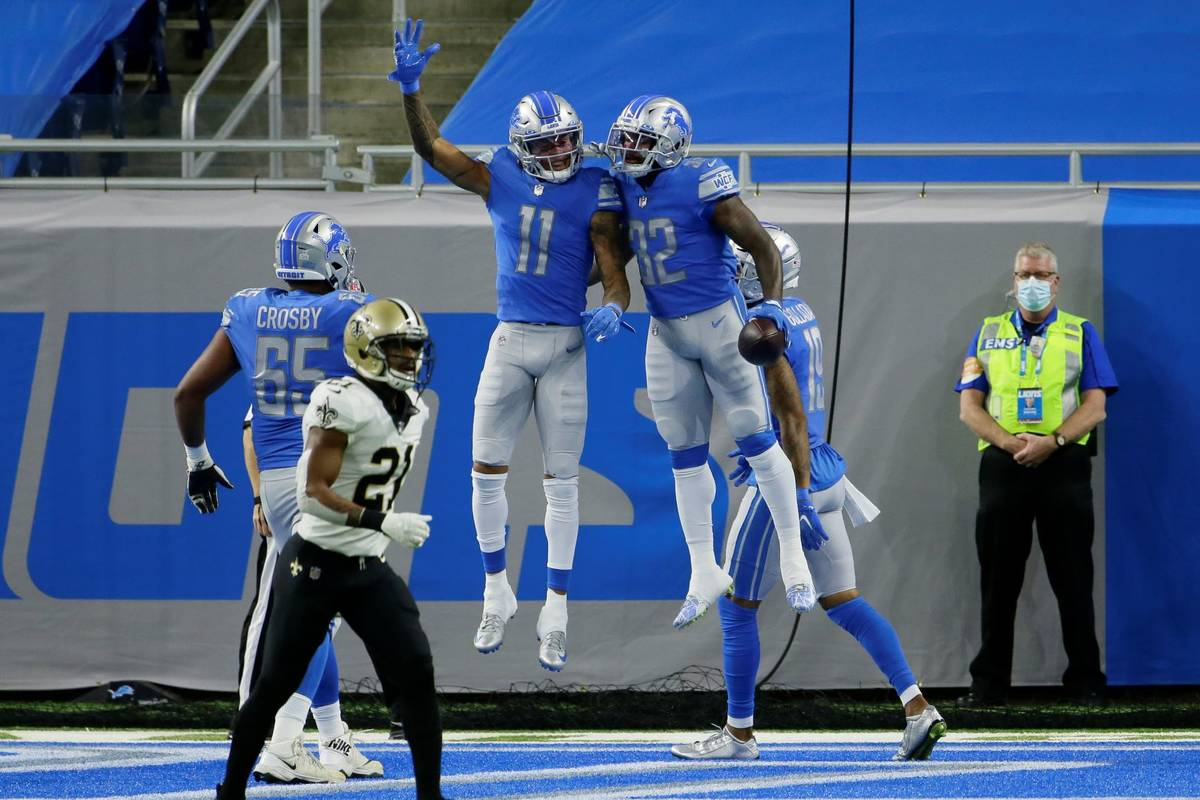 Detroit Lions running back D'Andre Swift (32) celebrates his 7-yard pass for a touchdown with t ...