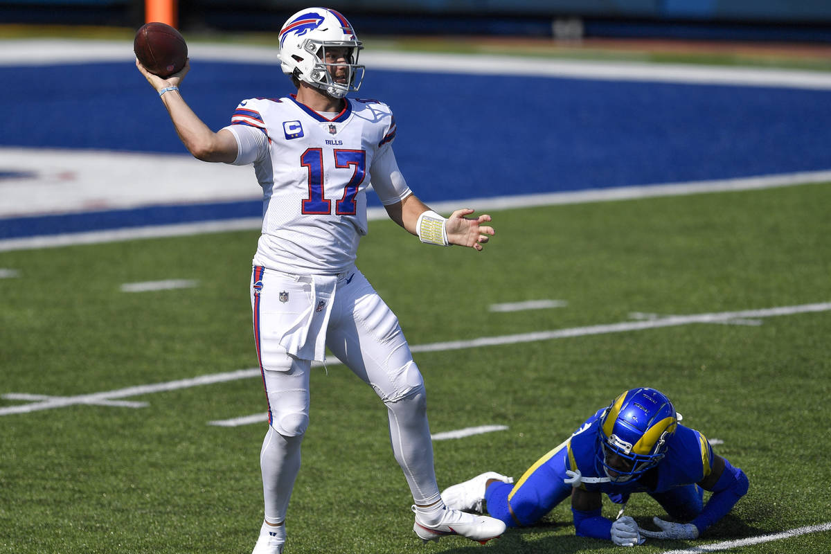Buffalo Bills quarterback Josh Allen, left, throws a pass after avoiding a tackle by Los Angele ...