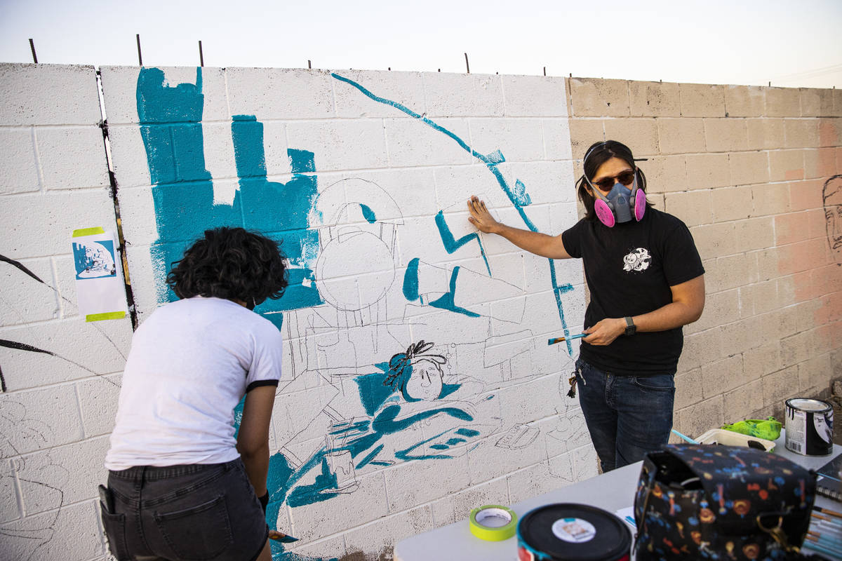 Artist Ross Takahashi, right, talks about his mural as he works alongside Dominique Chavira at ...