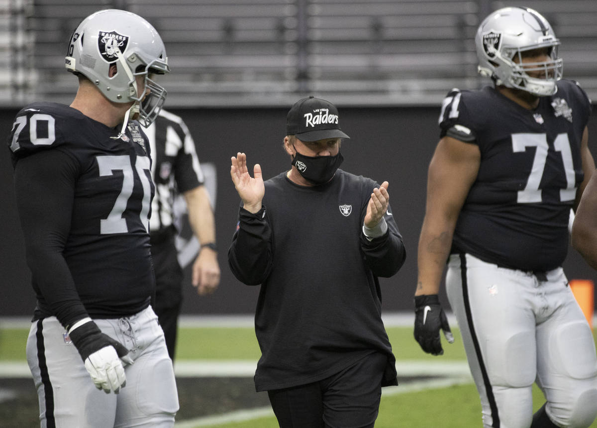 Las Vegas Raiders head coach Jon Gruden, middle, pumps up his team during warms up before the s ...