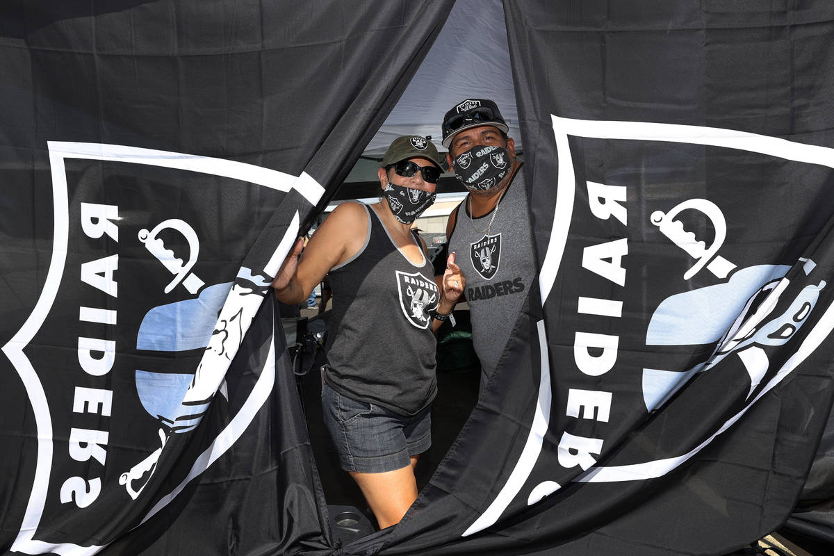 Maria Morales, left, and her husband Lorenzo Morales pose during a tailgate before an NFL footb ...