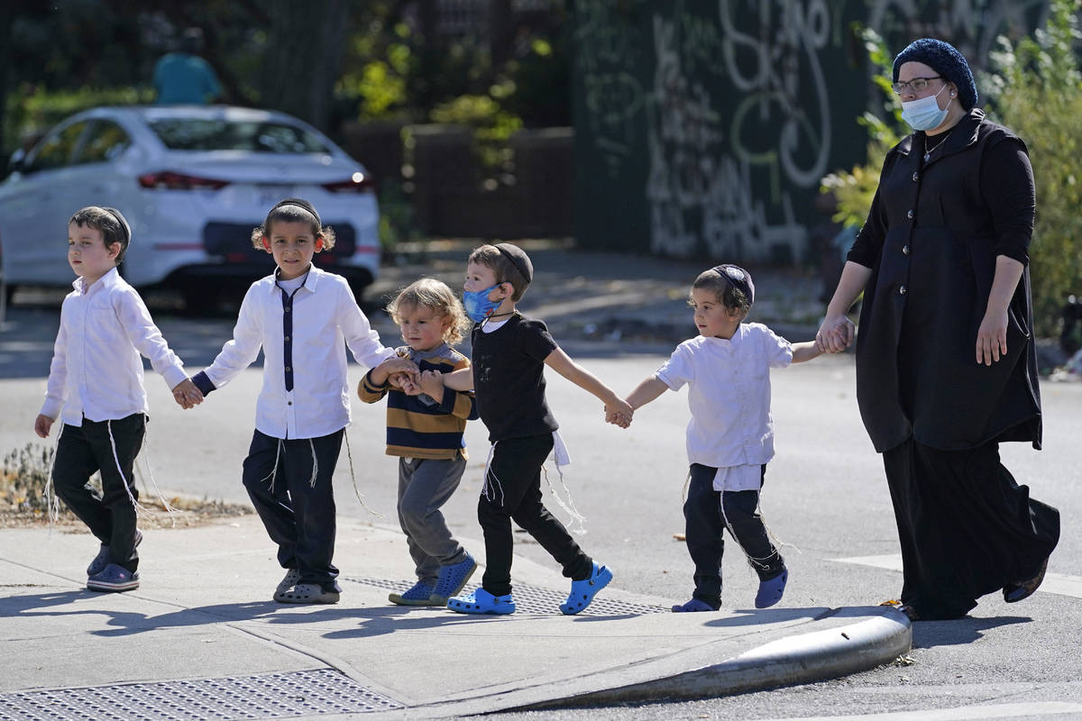 FILE- In this Sept. 28, 2020, file photo, a woman and a group of young children cross a busy st ...