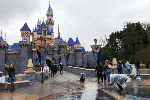 FILE - In this March 13, 2020 file photo, visitors take photos at Disneyland in Anaheim, Calif. ...