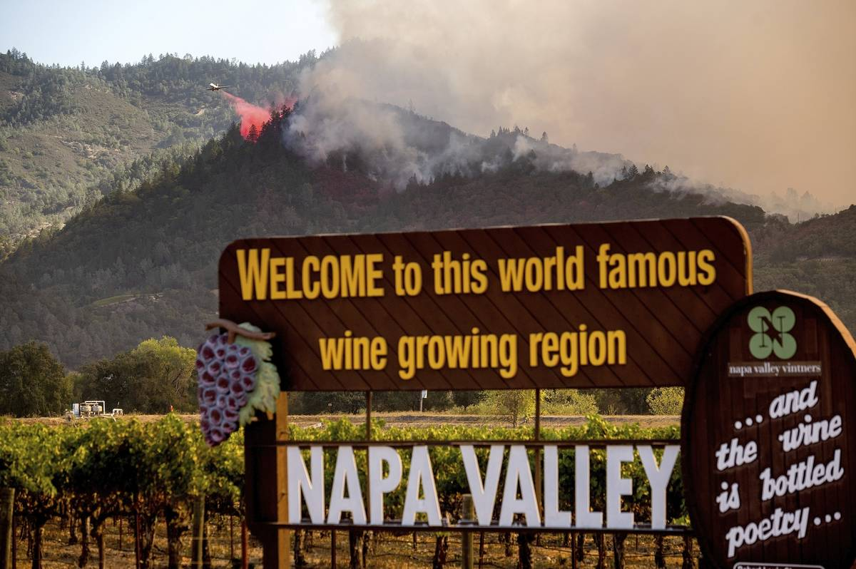 FILE - In this Sunday, Sept. 27, 2020, file photo, An air tanker drops retardant on the Glass F ...