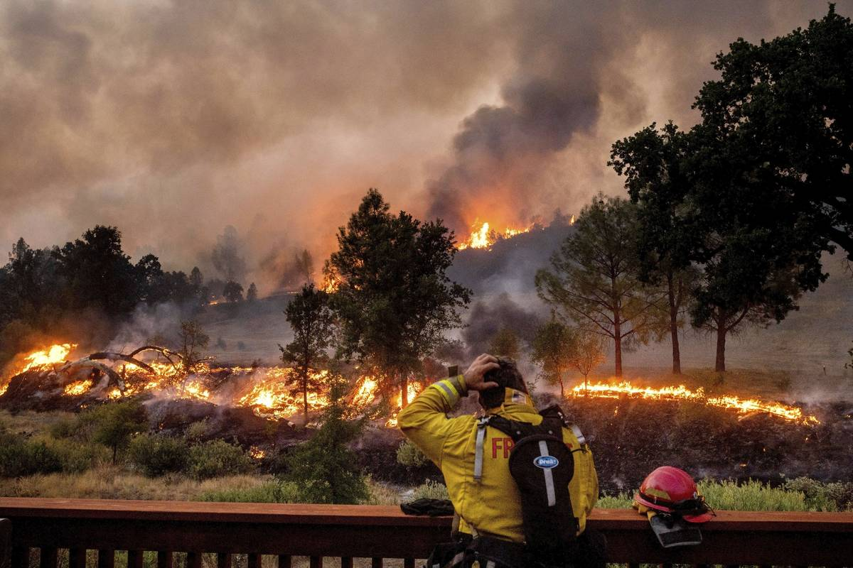 FILE - In this Aug. 21, 2020, file photo, a firefighter rubs his head while watching the LNU Li ...
