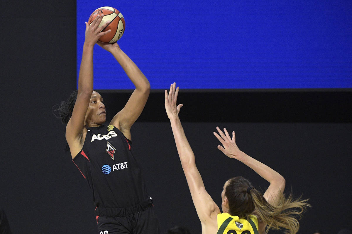 Las Vegas Aces center A'ja Wilson, left, goes up to shoot in front of Seattle Storm forward Bre ...