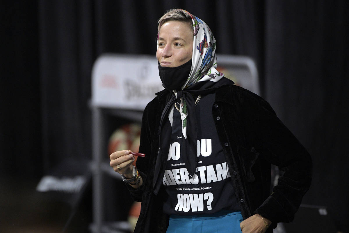 Professional soccer player Megan Rapinoe watches the first half of Game 2 of basketball's WNBA ...