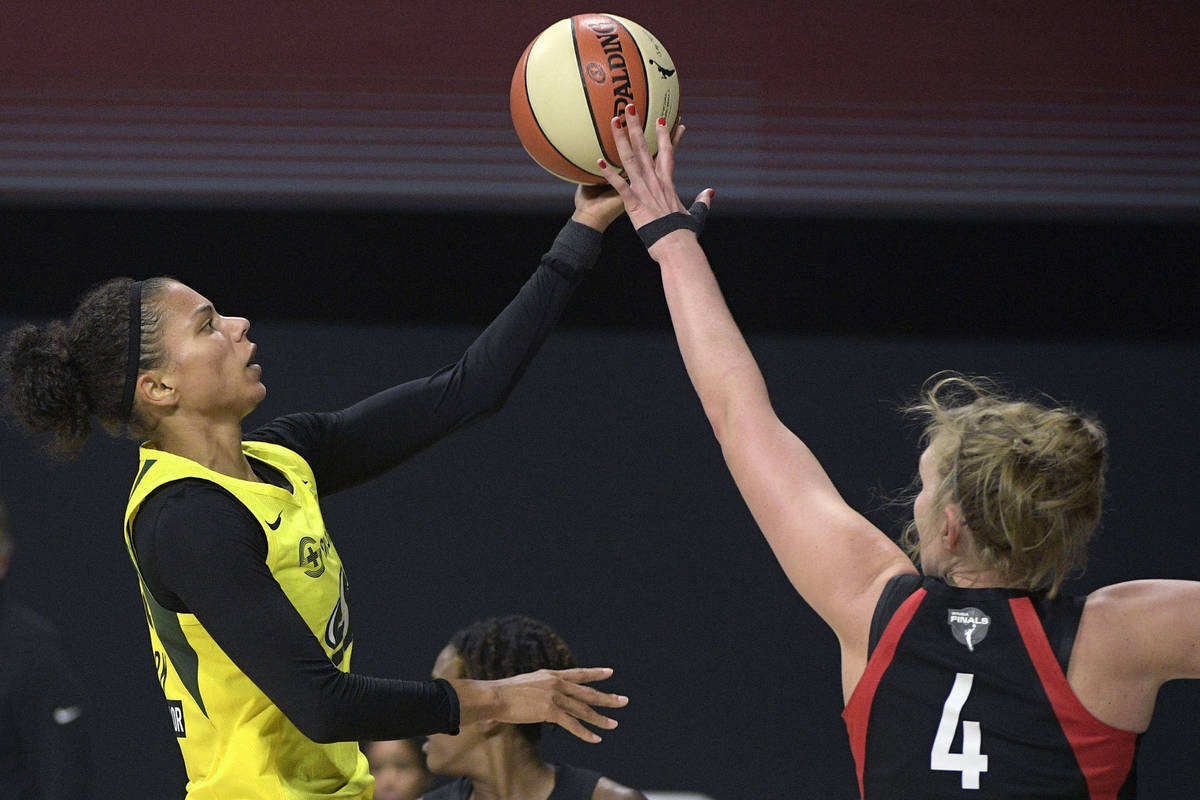 Seattle Storm forward Alysha Clark, left, goes up to shoot in front of Las Vegas Aces center Ca ...