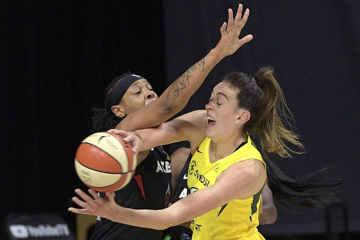 Seattle Storm forward Breanna Stewart, right, passes the ball while defended by Las Vegas Aces ...