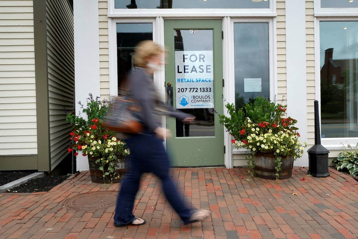 A shopper walks by one of several vacant retail spaces among the outlet shops in Freeport, Main ...
