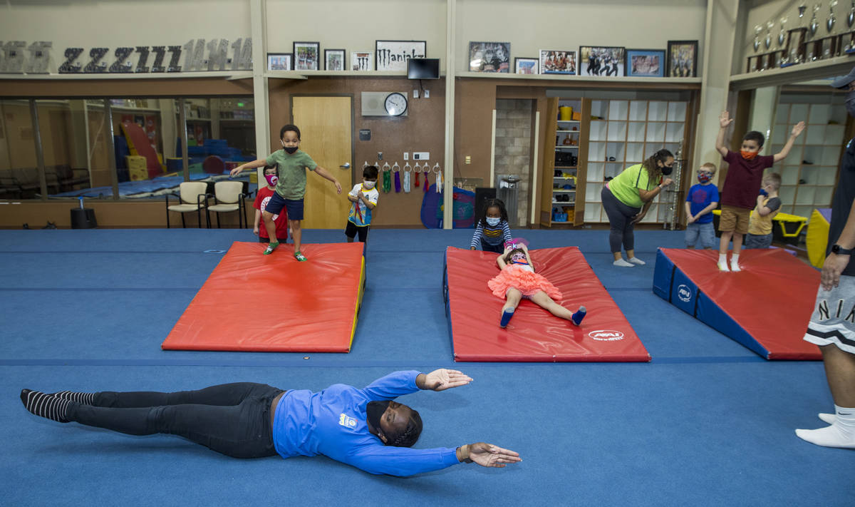 Instructor Iviana Ridgeway, below, shows kindergarteners a hotdog roll as their next exercise d ...