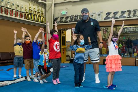 Instructor Mo Bonnet, center, encourages kindergarteners in standing jumps while exercising dur ...