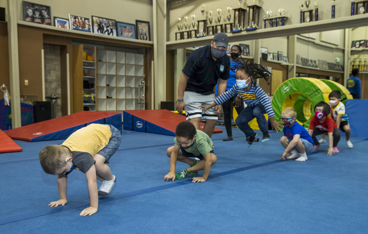 Instructor Mo Bonnet, center, encourages kindergarteners in frog jumps while exercising during ...