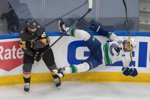 Vegas Golden Knights' Chandler Stephenson (20) checks Vancouver Canucks' Christopher Tanev (8) ...