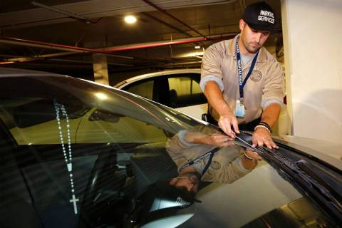 In this Nov. 22, 2016 file photo, Parking Enforcement Officer Logan Williams places a parking t ...