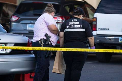 North Las Vegas police crime investigators collect evidence from an apartment where a man was f ...