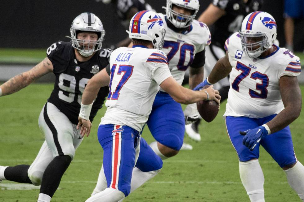 Las Vegas Raiders defensive end Maxx Crosby (98) puts pressure on Buffalo Bills quarterback Jos ...