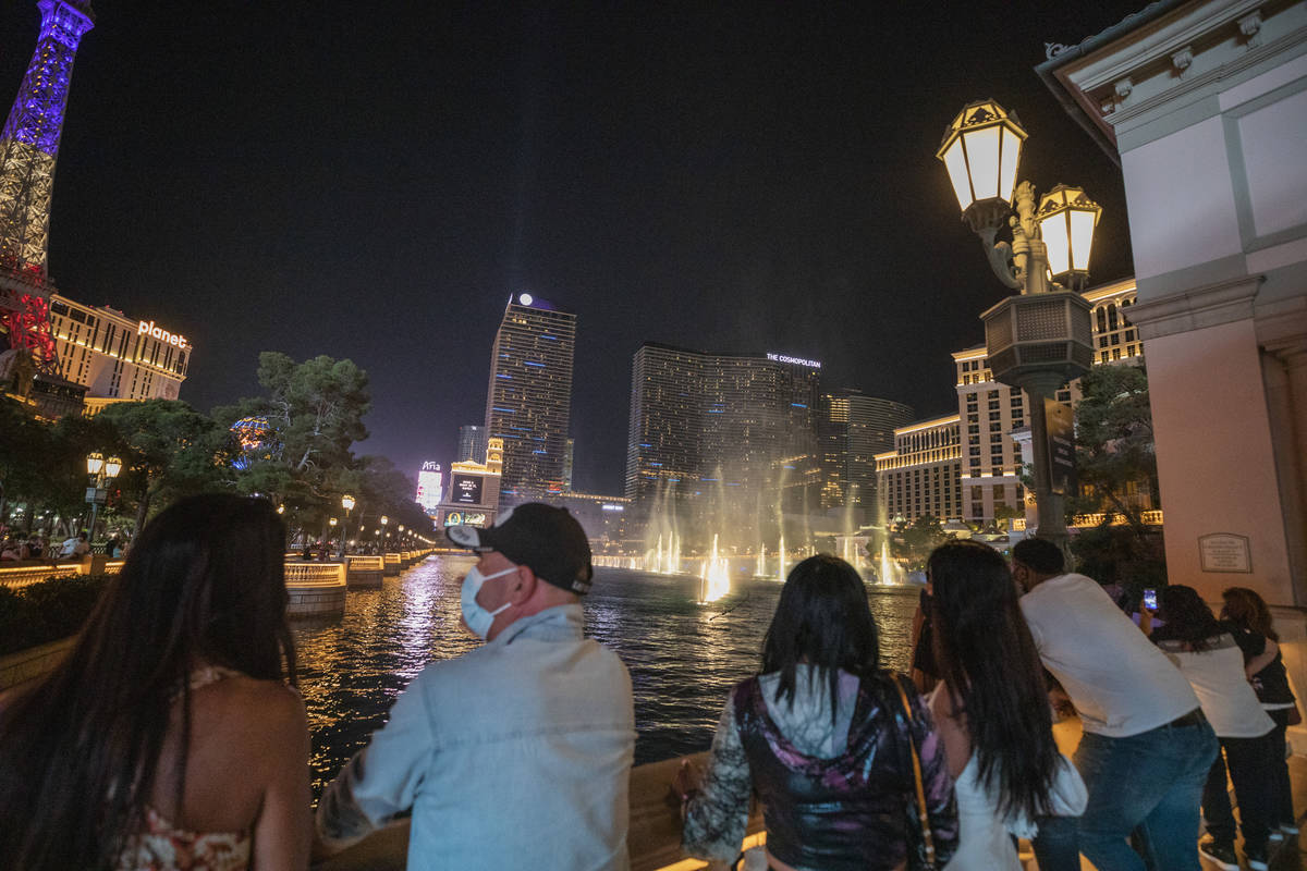 Tourists watch the Bellagio hotel and casino fountains, late Friday night on Oct. 7, 2020. (Eli ...